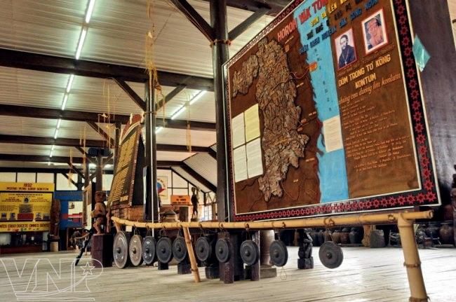 Une ensemble de gongs et une carte de Kon Tum en bois de pin exposées dans l'église