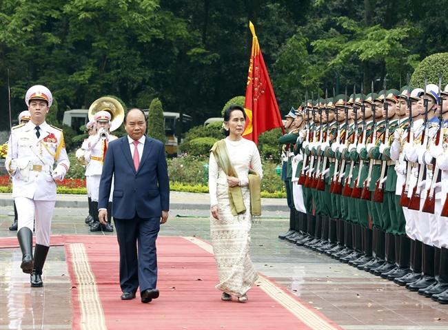 នារសៀលថ្ងៃទី១៩ ខែមេសា ឆ្នាំ២០១៨ នៅវិមានប្រធានរដ្ឋ លោកនាយករដ្ឋមន្រ្តី ង្វៀនស្វឹនភុក  (Nguyen Xuan Phuc) អញ្ជើញអធិបតីភាពពិធីទទួលស្វាគមន៍ លោកស្រីទីប្រឹក្សារដ្ឋ រដ្ឋមន្រ្តីការបរទេស និងជារដ្ឋមន្រ្តីការិយាល័យប្រធានាធិបតី នៃសាធារណរដ្ឋសហព័ន្ធមីយ៉ានម៉ា Aung San Suu Kyi បានអញ្ជើញមកបំពេញទស្សនកិច្ចជាផ្លូវការនៅវៀតណាម។ ក្នុងរូបថត៖ លោកនាយករដ្ឋមន្រ្តី ង្វៀនស្វឹនភុក (Nguyen Xuan Phuc) និងលោកស្រីទីប្រឹក្សារដ្ឋ រដ្ឋមន្រ្តីការបរទេសនិងជារដ្ឋមន្រ្តីការិយាល័យប្រធានាធិបតីមីយ៉ានម៉ា Aung San Suu Kyi ត្រួតកងពលកិត្តិយសក្នុងពិធីទទួលស្វាគមន៍។ រូបថត៖ ថុងញ៉ឹត/ ទីភ្នាក់ងារសារព័ត៌មានវៀតណាម