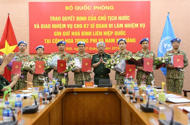 Seven officers from the Vietnam Peacekeeping Centre will be dispatched to the United Nations (UN) peacekeeping mission in the Central African Republic and South Sudan in 2018. In the photo: Deputy Defence Minister Senior Lieutenant General Nguyen Chi Vinh handed over the Presidents decisions to the officers at a ceremony in Hanoi on May 21. Photo: Duong Giang/VNA