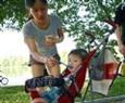 孩子跟母亲一起到公园避暑。