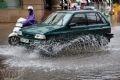 Một chiếc ôtô liều mình lao và con đường đầy nước.
