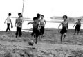 Playing football on the river's dry ground.