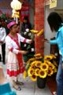 Une jeune fille de la Haute région choisissant des fleurs artificielles en soie.