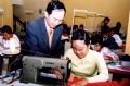 Volunteer teacher Tran Duyen Hai instructing an Agent Orange/Dioxin-affected girl on making garments at the Humanitarian Vocational Training Centre, under the Vietnam Association for the Support of the Disabled Children.