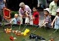 小孩操纵水上木偶很感兴趣。