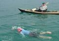 Bà Kimura Akiko, 72 tuổi, VĐV người Nhật, đang bơi vượt biển dưới sự hộ tống của thuyền kayak.
