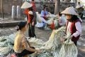 Au marché, on vend aussi les matières premières pour fabriquer le non : feuilles de latanier. . .