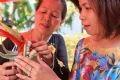 Mẹ dạy con gái cách trang trí một mâm hoa quả đẹp để dâng cúng thành hoàng làng.