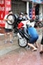 Repairing the motorbike by pouring water out of the exhaust pipe. Photo by Hoang Ha - VNP