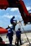 Obreros de la compañía vietnamita Cienco 1 estiran los cables bajo la supervisión técnica de la firma francesa Frey Shimet.