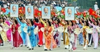 Female paraders carry the portrait of President Ho Chi Minh.