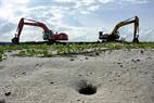 Những chiếc máy xúc miệt mài khai phá trên vùng bãi biển hoang sơ.