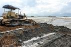 Cỗ máy xúc ủi đất lấn dần ra phía biển.