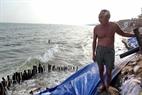 Ông lão tuyệt vọng đứng nhìn những đợt sóng biển đang gặm nhấm căn nhà nhỏ bé của mình.