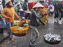 Một người buôn bán lẻ gánh cá ra chợ bán.