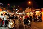 Chợ đêm Bến Thành tấp nập về đêm dưới ánh đèn vàng rực.