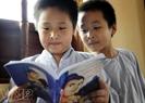 """Hai chú bé tìm hiểu về giáo lí nhà Phật từ cuốn """"Công đức của lòng tin""""."""