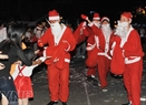Santa Clauses distribute gifts on a street in Ho Chi Minh City.