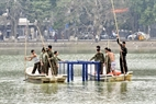 Đội giải cứu chuyển lồng sắt xuống nước để chuẩn bị cho cuộc giải cứu.