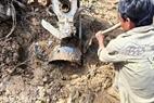 Một chiếc máy xay thóc đang được đào lên trong đống bùn.