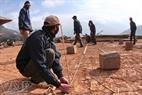 Gia đình nhà anh Quàng Văn Tuấn đo đạc lại phần đất được cấp ở bản mới để dựng nhà.