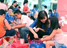 Volunteers help children make star lanterns. Photo: Cong Dat.