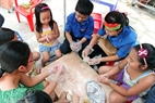 Volunteers teach children how to make moon cakes. Photo: Cong Dat.