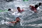 Local children swim in the sea.