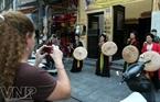 男女歌手们在古街演唱吸引外国游客的关注。