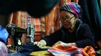 An old ethnic woman sews brocade products in the market.