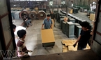 Workers move safes in the factory's production workshop.