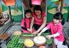 園児たちに、円筒形の粘っこい餅(北部の山岳地帯の民族の伝統的な食品)の包み方を教える先生