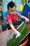 バイン・チュン(Banh Chung)を包むために、使用される葉を洗う男の子