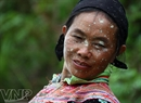 Sung Thi Tra, a Mong ethic woman in San Sa Ho Commune, with her face   spattered with mud after a day of working hard in her terraced field.