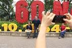 Turistas extranjeros toman fotos en las bellas calles decoradas con flores y banderas. Foto: Thong Hai