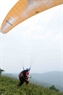 He is taking run up at a paragliding training.