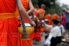 Each monk wears a bowl with a strap winding over his shoulder to contain alms offered by people.