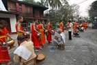 People hand out offerings to monks in front of Wat Xieng Thong Pagoda.