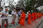 Many foreign tourists participate in the morning alms giving ritual.