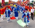 Un groupe de 84 enfants portant des costumes bleus conduit par un commandant procède des drapeaux.