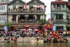 Des milliers de gens du village de Tây Tuu encouragent les équipes de régate sur les deux rives.