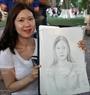 Chị  Lee Hye, du khách đến từ Hàn Quốc thích thú với bức ký họa vừa hoàn thành của mình.