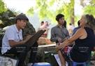 Du khách nước ngoài đang được các họa sĩ vẽ tranh ký họa bên Hồ Gươm.