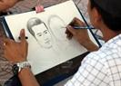 Một họa sĩ đang hoàn thiện bức ký họa đôi cho du khách.