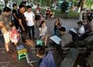 Du khách thích thú xem các họa sĩ vẽ tranh ký họa bên Hồ Gươm.