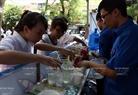 Điểm cấp phát nước và bánh mỳ miễn phí của nhóm sinh viên tình nguyện tại một điểm thi trên đường Lý Thường Kiệt. Ảnh: Thông Thiện