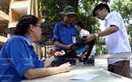Группа студентов-добровольцев факультета информационных технологий (Политехнический Университет Ханоя) организовала точки для хранения сумок и телефонов экзаменующиxся перед входом в экзаменационный зал. Фото: Тхонг Тхиен