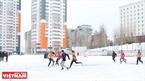 Các bạn trẻ chơi bóng trên sân phủ đầy tuyết trắng.