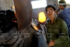 Pham Xuan Duong who has 30 year experience checks the quality of molten glass. Photo: Tran Thanh Giang/VNP