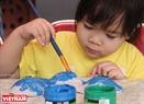 Bé Đỗ Quyên (4 tuổi) say mê tô màu mặt nạ. Ảnh: Dư Phiên